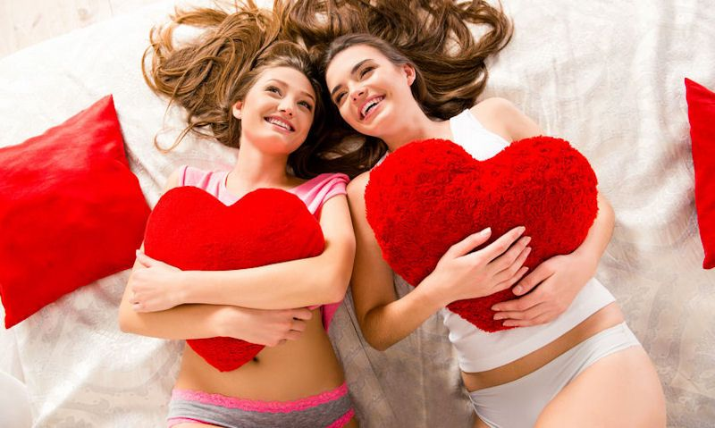 Women wearing hipster, cheekies in bed with heart pillows