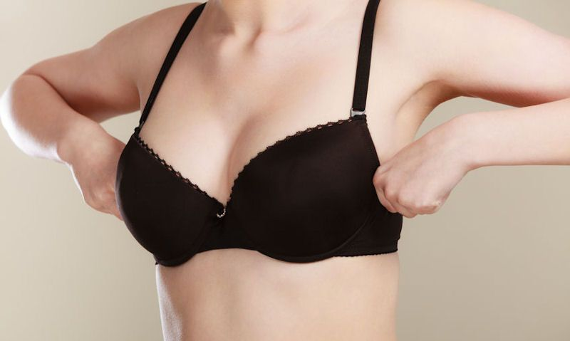 Women holding onto bra band to prevent curling