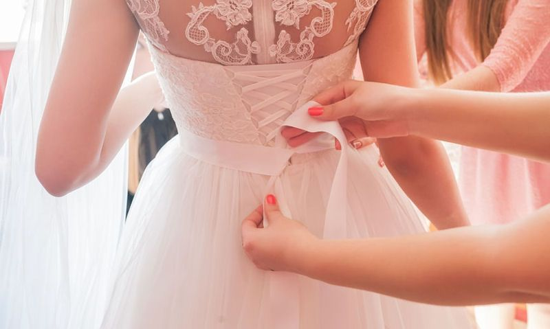 Bridesmaid tying brides wedding dress bow
